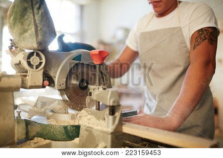 Specialist in carpentry sawing wooden planks with power tool or machine