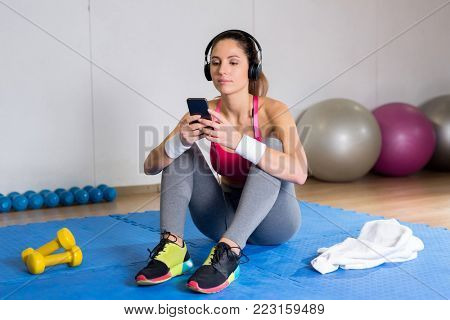 Young attractive woman choosing soundtracks from playlist in her smartphone between workouts