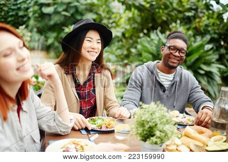 Group of intercultural friends laughing during festive dinner on summer day in the garden