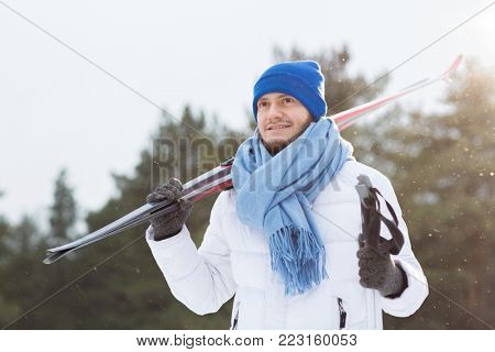 Young sportsman in white winter jacket, blue scarf and beanie hat holding pair of skis while spending time in winter park