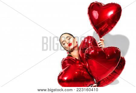 Valentine Beauty girl with red air balloons laughing, isolated on background. Beautiful Happy Young woman. Holiday party. Kiss.Sexy Joyful model having fun, holding, celebrating with red color balloon