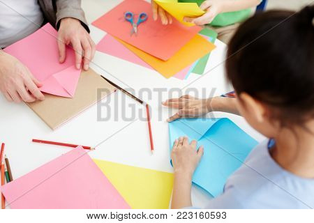 Secondary school learners using pink and blue paper while making origami