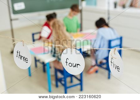 Round paper cards with words 'three', 'four' and 'five' hanging on thread with group of schoolkids on background