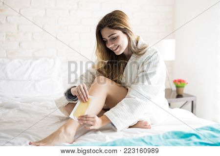 Happy girl removing her body hair using waxing strips and feeling no pain at all