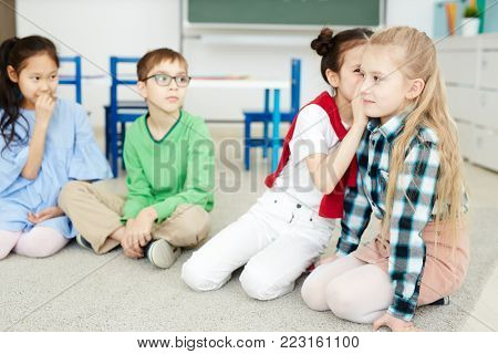 Group of young classmates whispering each other curious phrase or sentence while playing leisure game
