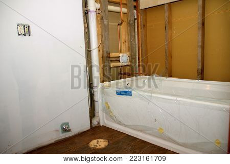 A bathroom remodeling project ready for tile to be put around the tub poster