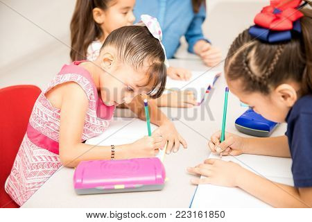 Group of preschool students working on a writing assignment in a classroom