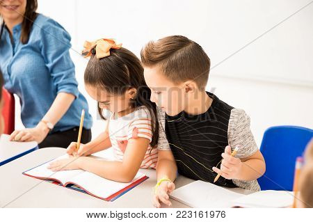 Caucasian preschooler trying to copy the work of a classmate while doing a writing assignment in a classroom