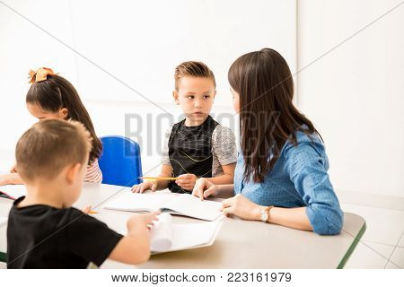 Little kid paying attention to his teacher while she explains a writing assignment in a classroom
