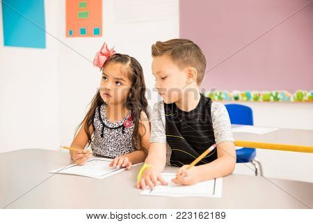 Good looking little kid trying to cheat on a math assigment in a preschool classroom