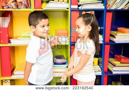 Profile view of a shy little boy and a girl flirting with each other while standing in front of a classroom locker