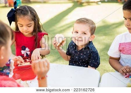 Portrait of a little boy eating a sandwich and smiling during his lunch break at kindergarten