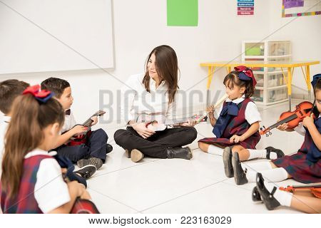Pretty preschool teacher teaching music to  a group of students sitting on the classroom floor