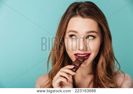 Portrait of a smiling brown haired woman with bright makeup eating chocolate bar isolated over blue background