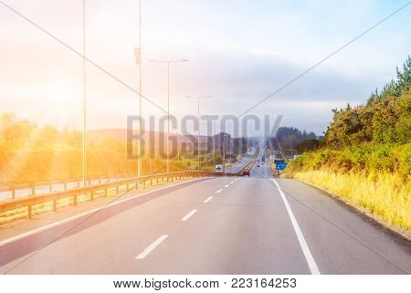 Hilly landscape with intercity  highway against the shiing sun