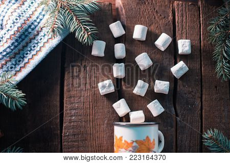 White cup with marshmallow on a wooden background