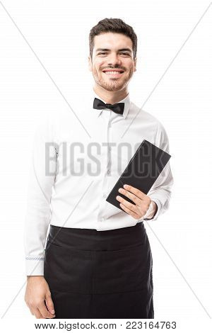 Good looking Hispanic waiter dressed formally and carrying a restaurant menu