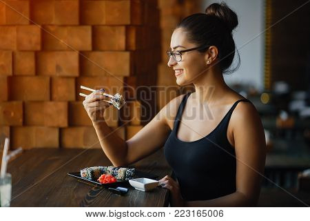 girl eating sushi at the restaurant by the window