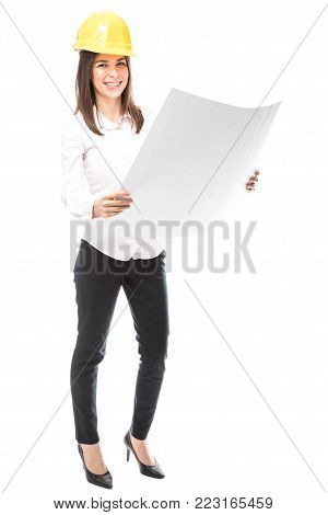 Full length portrait of a beautiful young Hispanic woman working as an architect wearing a helmet and reviewing some building plans