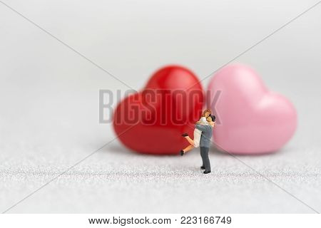 Valentines or wedding card and background by miniature people sweet couple, red and pink heart shapes on glitter reflective particle white paper, Valentine's day celebration is 14th February.
