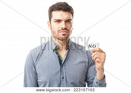 Hispanic young man looking serious and holding a small sign with the work NO on it