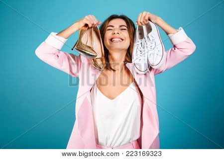 Portrait of a delighted woman dressed in pink suit holding pair of high heels shoes and pair of sneakers isolated over blue background