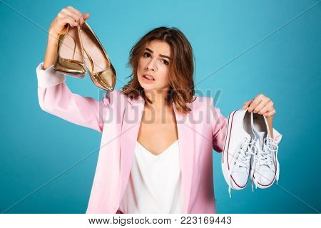 Portrait of a puzzled woman dressed in pink suit holding pair of high heels shoes and pair of sneakers isolated over blue background