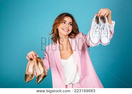 Portrait of a smiling woman dressed in pink suit holding pair of high heels shoes and pair of sneakers isolated over blue background