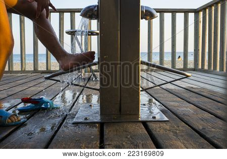 Child removing the sand from the foot on the beach shower, Islantilla, Huelva, Spain