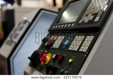 CNC metalworking machine with the control panel in the foreground. Selective focus.