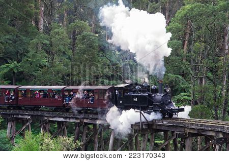 Puffing Billy steam train crossing a trestle bridge near Belgrave in the Dandenong Ranges. Puffing Billy is a popular tourist attraction.