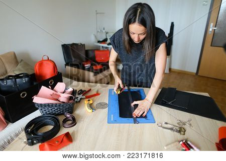 Young woman working with strap at clothing repair, man requested master to change snap on belt. Concentrated female sitting near table with scissors and special tools in well-lit room. Concept of handicraft, workshop or mending.