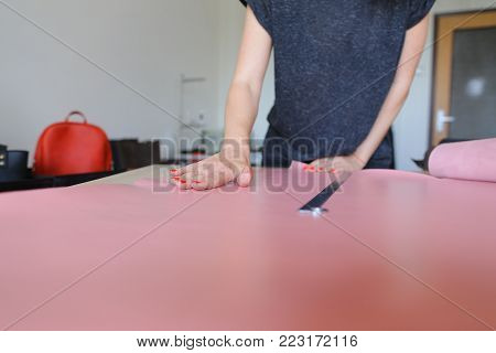 teacher demonstrating future seamstresses how to work with leather, young woman teaching to make bags. Female with red nails wearing grey T-shirt standing near table in workshop and preparing to cut necessary pattern. Concept of sewing,