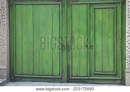 A street view of colorful green entry doors to a building in San Miguel de Allende, Mexico.