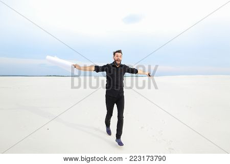 chemist pass quest from friends for birthday, fellow get poster with congratulations jumping for joy. Bearded guy has good mood walking running among sands. Concept of beautiful landscapes, innovative technologies or stylish outfits.