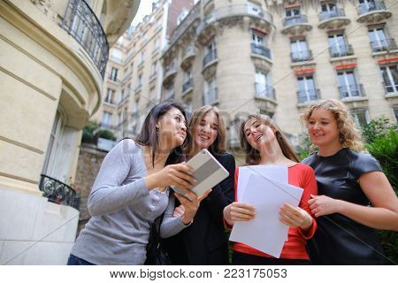 International students paying by tablet with card in   with university building background. Concept of education exchange programs and tuition fee.