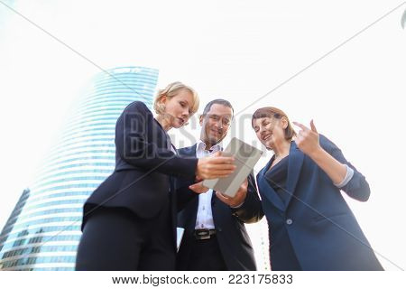 Satisfied business team members speaking outdoors in  . Concept of biz partners enjoying successful result. Businesswomen talking with male boss and smiling.
