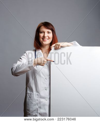 Image of smiling female doctor in white robe and with phonendoscope points finger at blank piece of pape