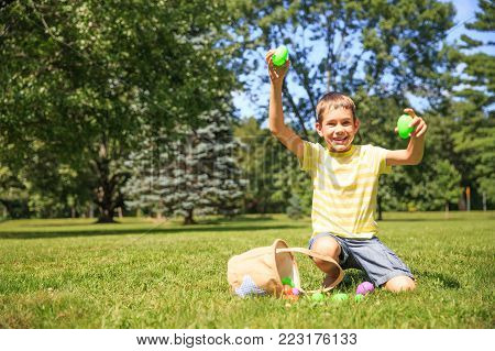 boy enjoys the result of the Easter Egg Hunt. the child is sitting on the grass with the Easter eggs in his hands. The concept of Easter Egg Hunt