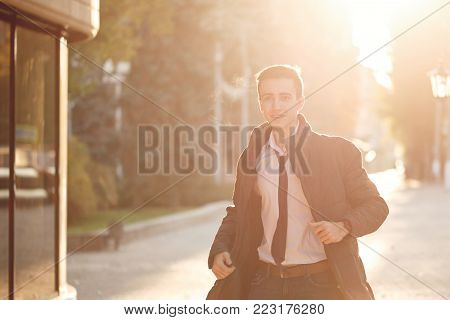 Stylish guy a teenager in a tie and jacket to hurry up on a date. He walks along the alley. Backlight of the setting sun