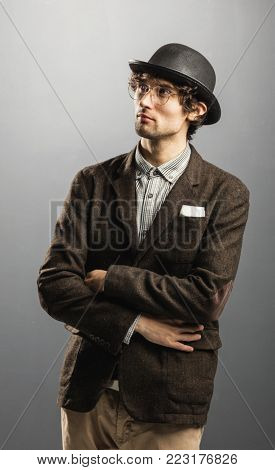 Pensive man in retro clothes and hat staring at the space. Vintage fashion.