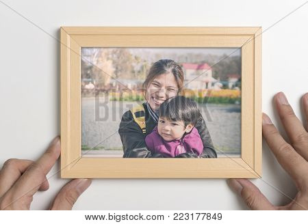 Daddy hand holding a picture of mother and son  in frame