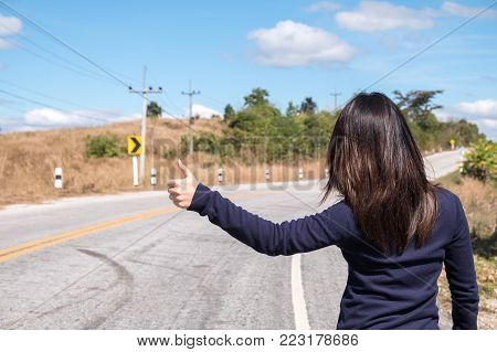 A Young Asian Woman Hitchhiking On The Side Of Road
