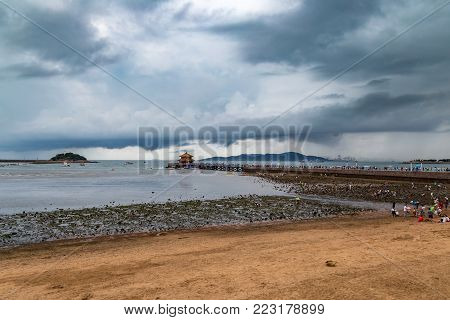 Zhanqiao Pier under a stormy sky in summer, Qingdao, Shandong, China. Zhanqiao is the famous pavilion displayed on the bottles of Qingdao beer