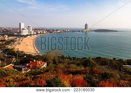 View of bathing beach N1 from the hill of Xiao Yu Shan Park in autumn, when the hill is covered in red leaves. Qingdao, Shandong province, China