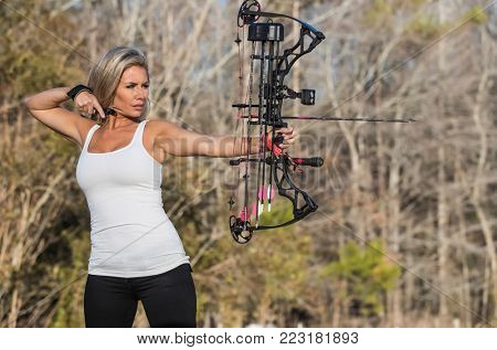 A beautiful blonde model posing with a bow and arrow outdoors