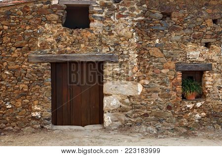 Facade of old house with windows and wooden door. Cáceres, Spain.