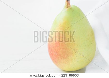 Single Ripe Organic Pear in Pastel Green Yellow Red Colors Linen Fabric on White Wood Background. Elegant Minimalist Japanese Style. Creative Image for Social Media Blog Product Branding. Copy Space