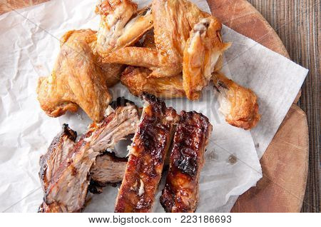 juicy barbeque pork ribs and dry chicken wings with glaze and hot sauce on the side