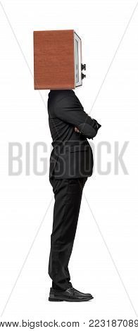 An isolated businessman stands in a side view with crossed arms and a TV box instead of his head. Business and technologies. Advertizing. Obsolete strategies.